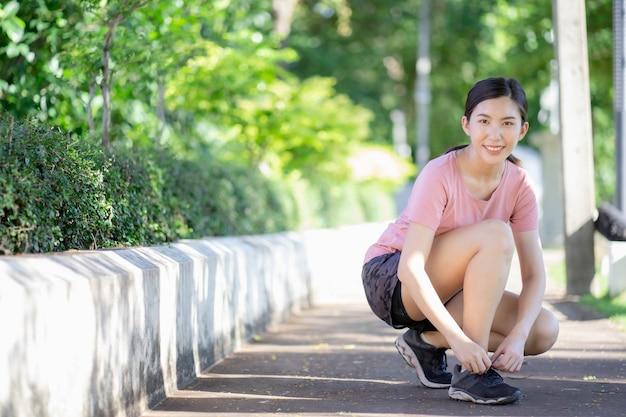 Asiatische frau, die ihre schnürsenkel bindet, bevor sie im park joggen geht.