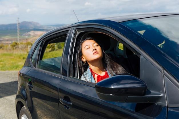 Asiatische frau, die im auto sitzt und sonne genießt