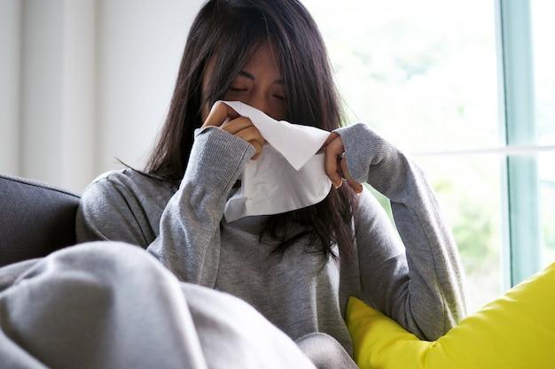 Asiatische frau, die im gewebe niest. krankheit, auf dem sofa liegend