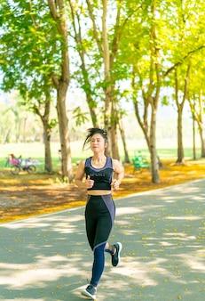 Asiatische frau, die im park joggt und läuft