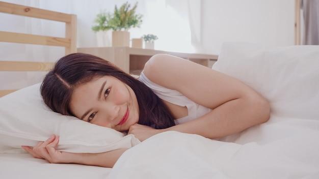 Asiatische frau, die im schlafzimmer auf dem bett liegt, lächelt