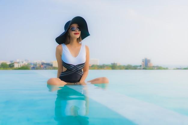 Asiatische frau, die im swimmingpool sich entspannt