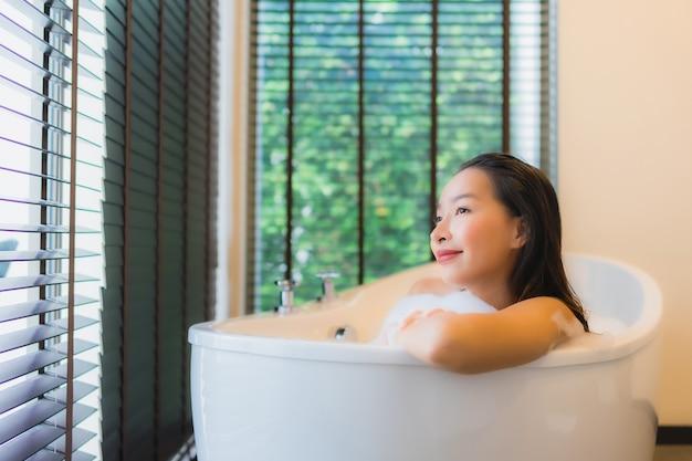 Asiatische frau, die in der badewanne sich entspannt