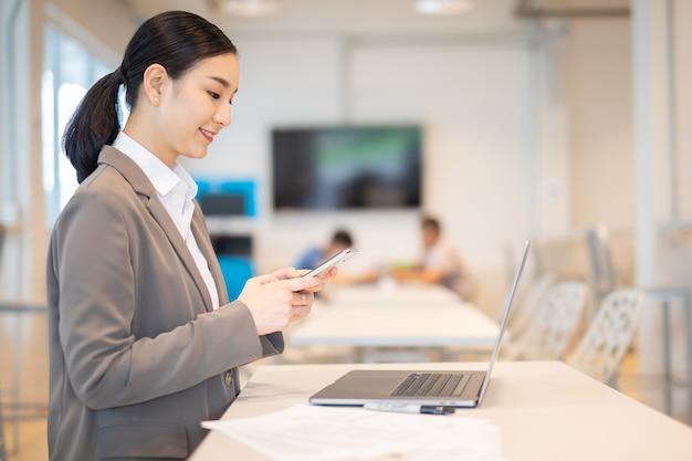 Asiatische frau, die in einem modernen büro arbeitet, das einen laptop verwendet