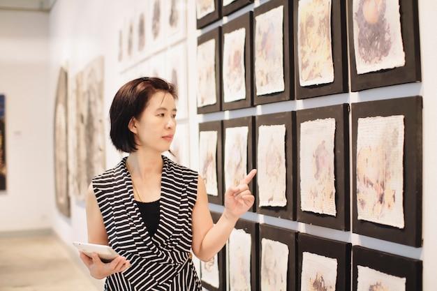 Asiatische frau, die in einer kunstgalerie vor bunt gerahmten gemälden steht, die an einer wand ausgestellt sind
