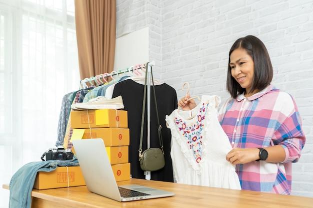 Asiatische frau, die intelligentes handy verwendet, das live-verkauf von online-modekleidung nimmt