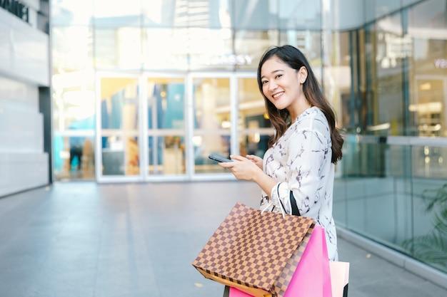 Asiatische frau, die intelligentes telefon und lächeln mit einkaufstaschen überprüft, genießen im einkaufszentrum