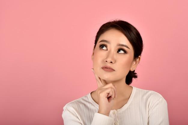 Asiatische frau, die isolierte rosa wand denkt, porträt des gesichtsausdrucks der frau, der frage fühlt und sich wundert.