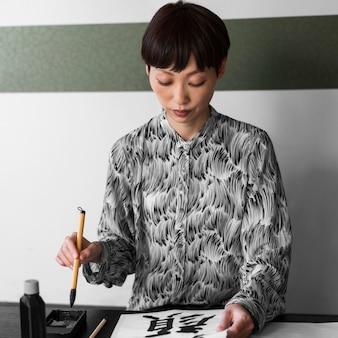 Asiatische frau, die japanische buchstaben malt