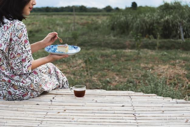 Asiatische frau, die käsekuchen mit tasse kaffee mit landschaftsblick isst.