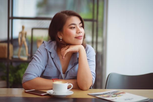 Asiatische frau, die kaffee im kaffeehauscafé trinkt und handy benutzt