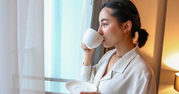 Asiatische frau, die kaffee trinkt und aus dem fenster im haus schaut.