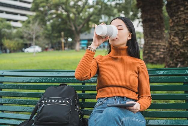 Asiatische frau, die kaffee trinkt und eine tablette verwendet.