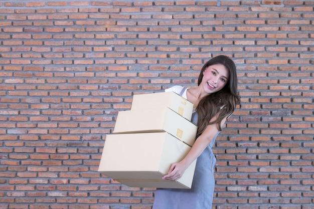 Asiatische frau, die kisten von paketen in ihrem online-einkaufsgeschäft zu hause packt