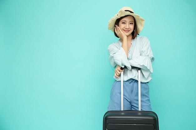 Asiatische frau, die koffer lokalisiert hält