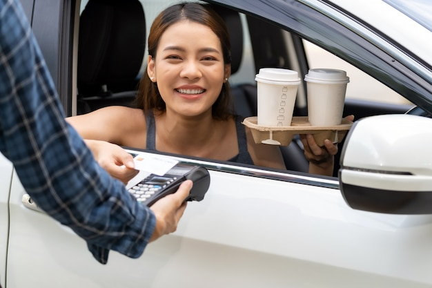 Asiatische frau, die kontaktlose zahlung mit kreditkarte für fahrt durch kaffee macht