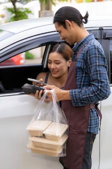 Asiatische frau, die kontaktlose zahlung mit kreditkarte für herausnehmen fahrt durch essen macht