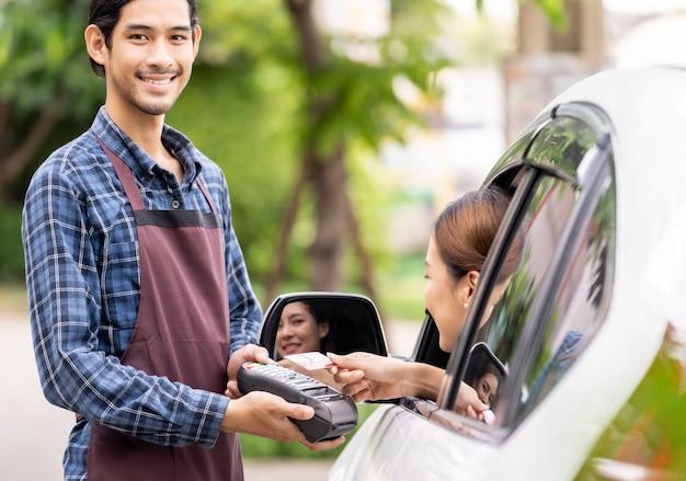 Asiatische frau, die kontaktlose zahlung mit kreditkarte macht