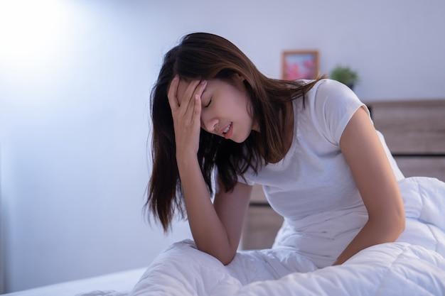 Asiatische frau, die kopfschmerzen hat, kann migräne morgens auf dem bett sein