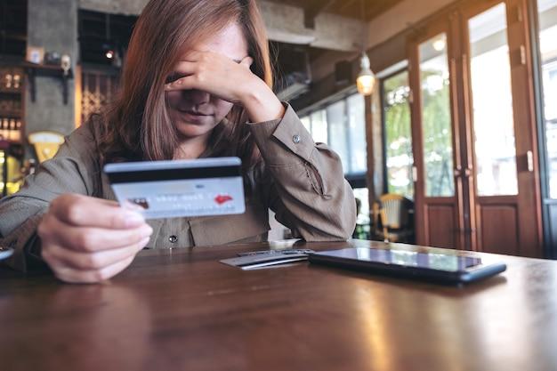 Asiatische frau, die kreditkarte mit dem gefühl gestresst und pleite hält, handy auf dem tisch