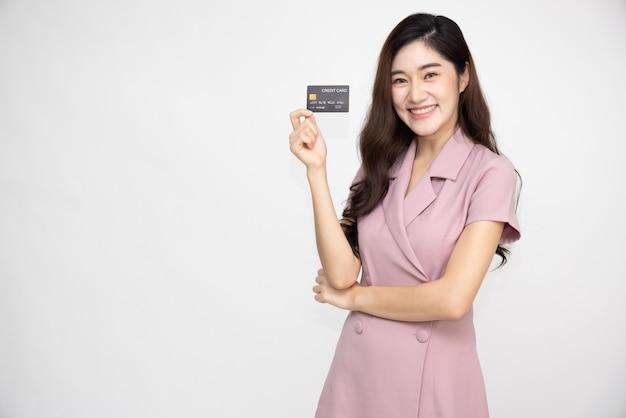 Asiatische frau, die kreditkarte zeigt, um zahlungen zu tätigen oder online-geschäfte zu bezahlen