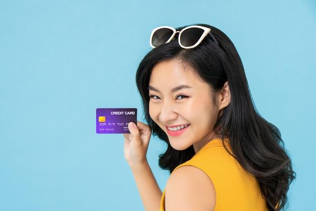Asiatische frau, die kreditkarte zeigt