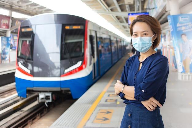 Asiatische frau, die kurze haare hat und blaues hemd trägt, steht arm verschränkt, während sie auf den zug am bahnhof wartet