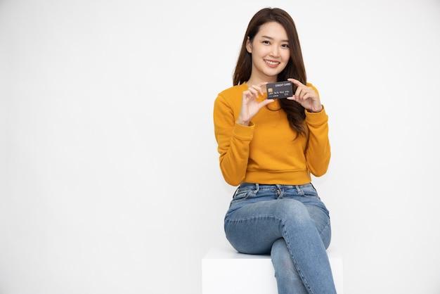 Asiatische frau, die lächelnd zeigt, dass sie eine kreditkarte für die zahlung oder das bezahlen von online-geschäften vorlegt