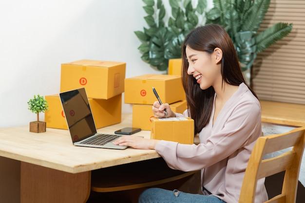 Asiatische frau, die laptopschreiben auf paketbox arbeitet, die zu hause büro für online-marketing-kleinunternehmer arbeitet