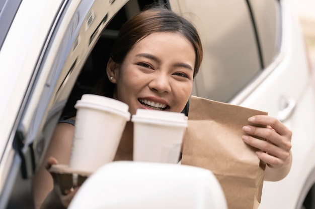 Asiatische frau, die lebensmittelbeutel vom durchfahrtsrestaurant hält