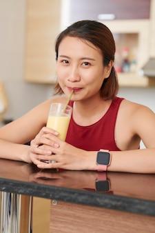 Asiatische frau, die leckeren fruchtcocktail trinkt
