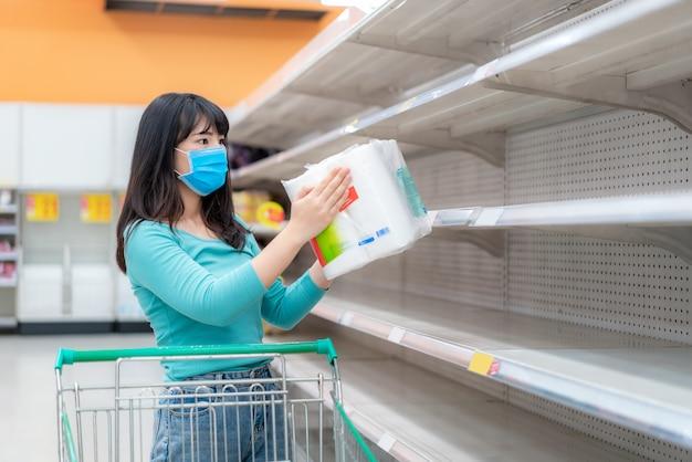 Asiatische frau, die leere toilettenpapierregale des supermarkts inmitten von covid-19-coronavirus-ängsten betrachtet, käufer, die panik kaufen und toilettenpapier für eine pandemie lagern.