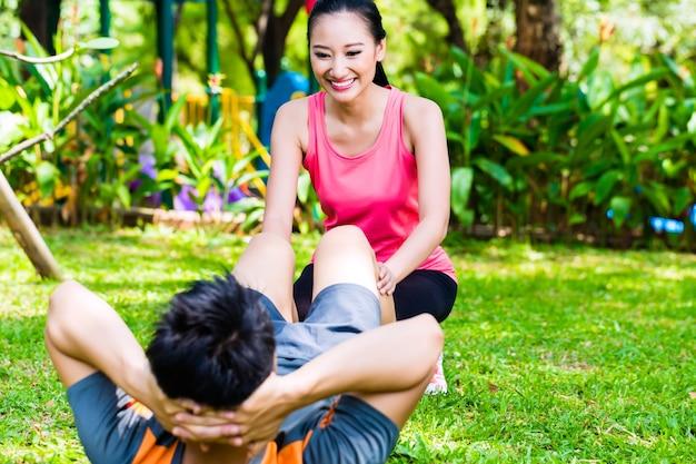 Asiatische frau, die mann mit streckübungen im park für fitness hilft