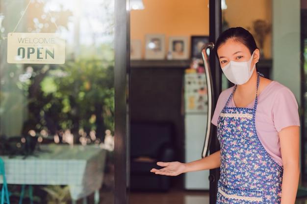 Asiatische frau, die maske steht mit offenem schild am fenster im kaffeehaus steht.