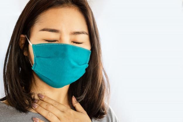 Asiatische frau, die maske trägt, die unter halsschmerzen leidet Premium Fotos