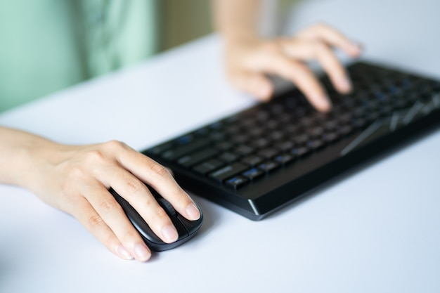 Asiatische frau, die maus und tastatur verwendet, um zu arbeiten Premium Fotos