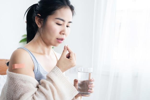 Asiatische frau, die medikamente einnimmt, nachdem sie den impfstoff coronavirus erhalten hat