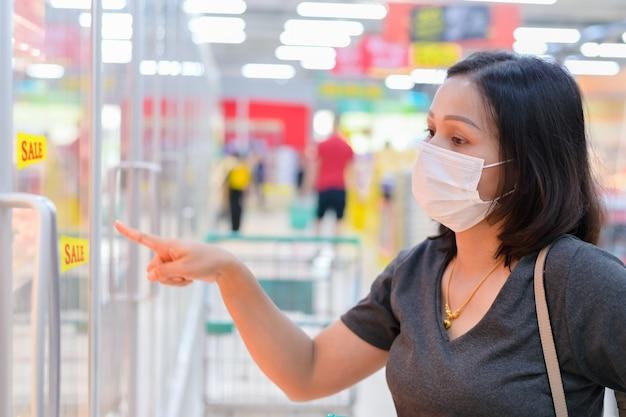 Asiatische frau, die medizinische einwegmaske trägt, die im supermarkt während der coronavirus-epidemie einkauft