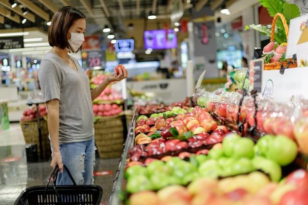 Asiatische frau, die medizinische maskeneinkäufe trägt