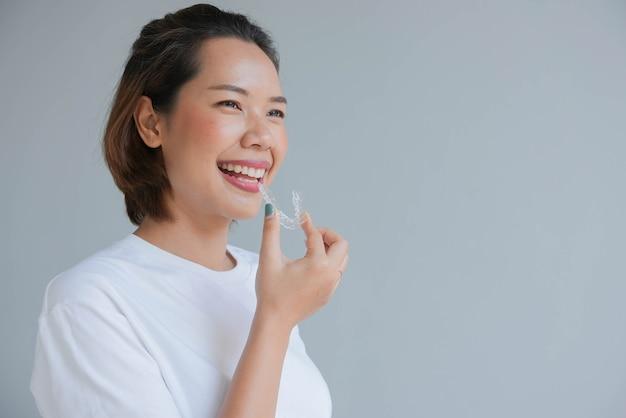 Asiatische frau, die mit der hand lächelt, die den zahnschienenhalter unsichtbar hält