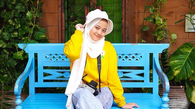 Asiatische frau, die mit einer kamera sitzend reiste, lächelte