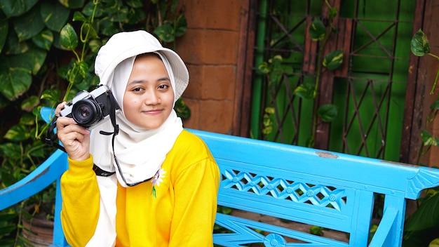 Asiatische frau, die mit einer kamera sitzend reiste, lächelte Premium Fotos