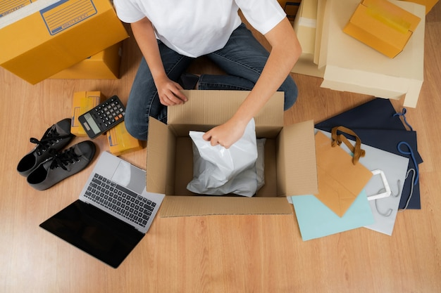 Asiatische frau, die mit einer schachtel des produkts arbeitet, online-ideenkonzept verkaufend, online-verkäufergeschäftsshop zu hause