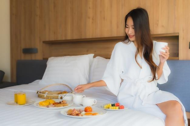 Asiatische frau, die mit frühstück auf bett genießt