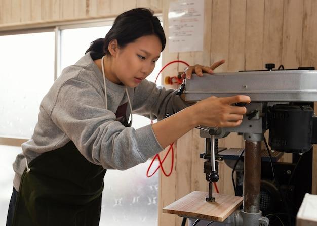 Asiatische frau, die mit holz arbeitet
