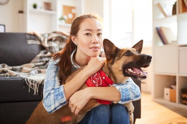 Asiatische frau, die mit hund aufwirft