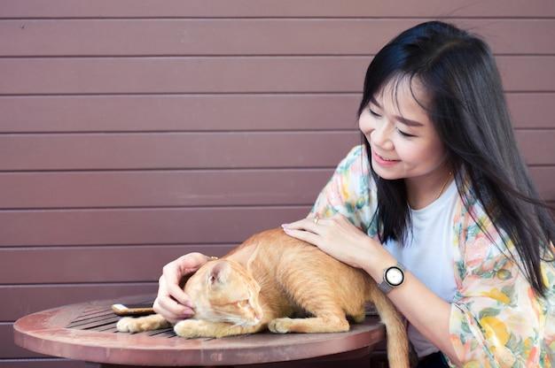 Asiatische frau, die mit katze im haus spielt