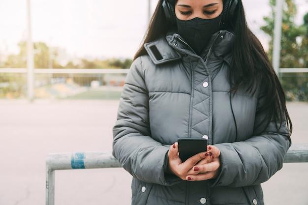 Asiatische frau, die mit kopfhörern und schützender gesichtsmaske auf das handy schaut, kopienraum lifestyle