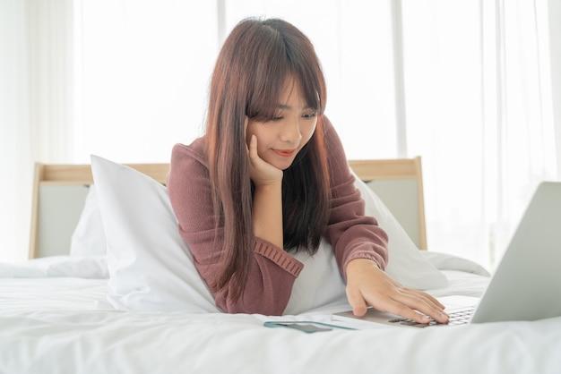 Asiatische frau, die mit laptop auf bett zu hause arbeitet