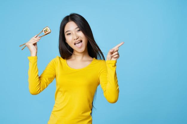 Asiatische frau, die mit lebensmittelporträt, sushi aufwirft